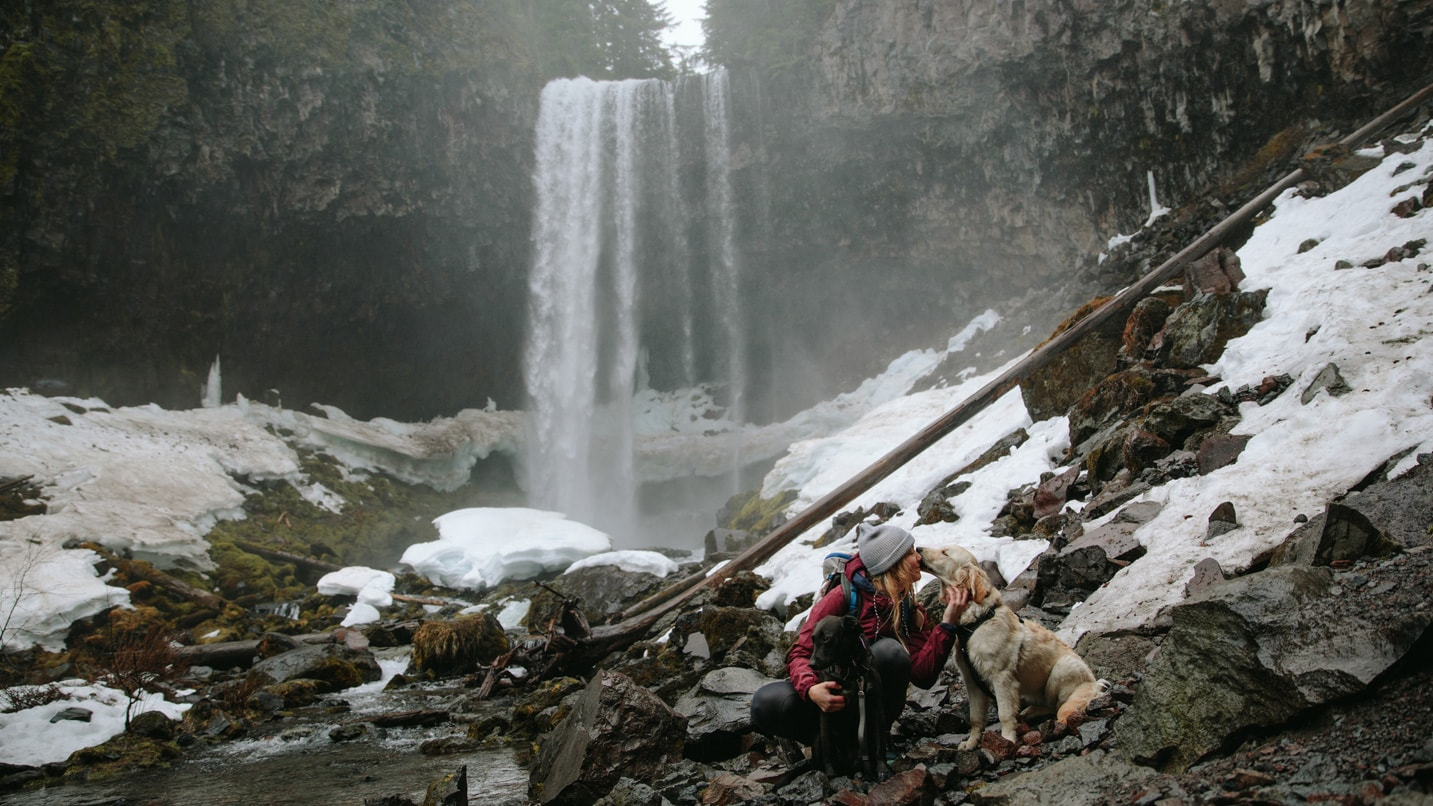 A woman petting her dog with a snowy waterfall in the background