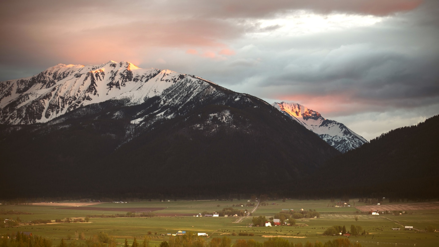 A pastoral landscape with snowcapped mountains at sunset