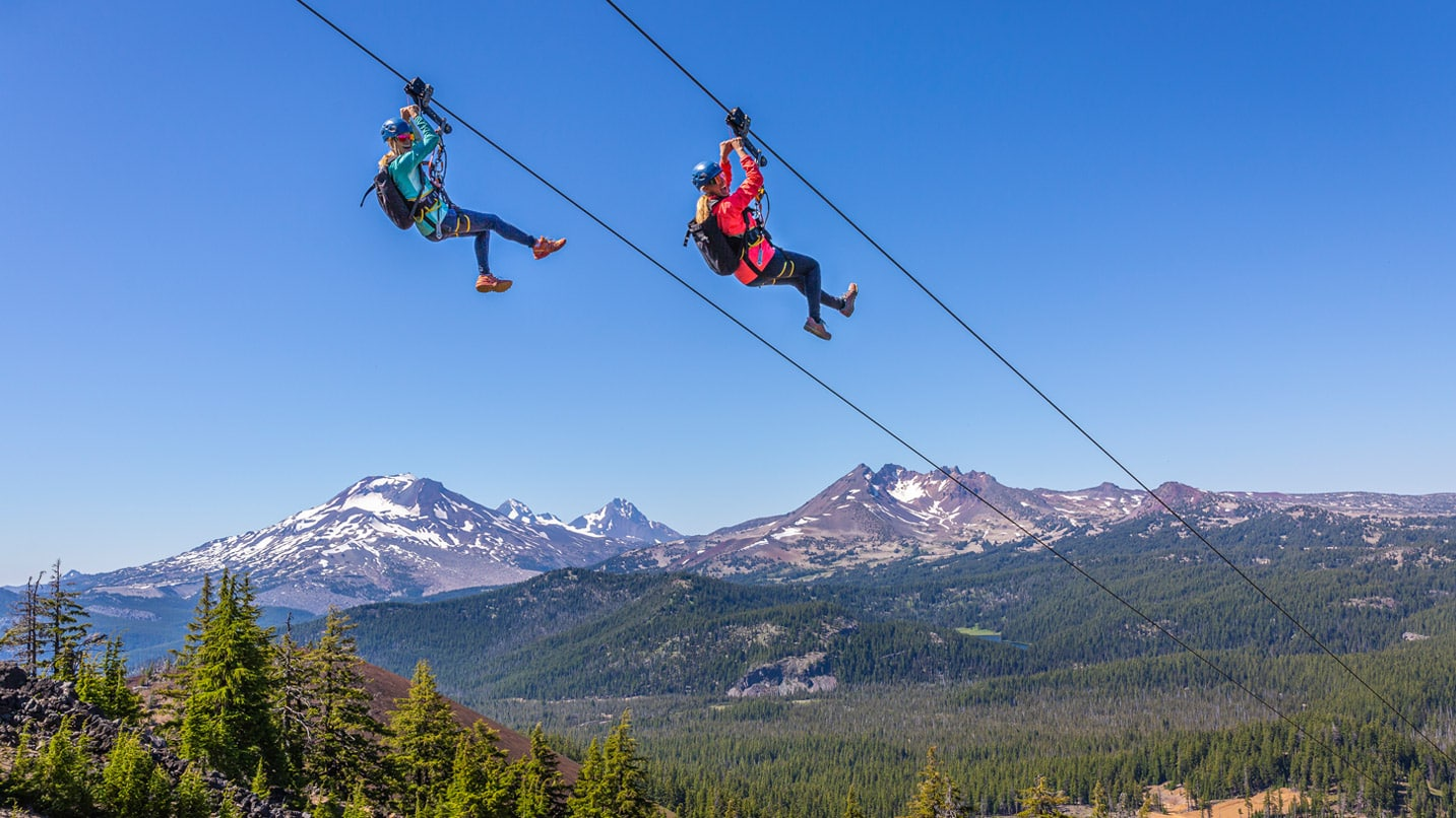 Two people on a zip lines with snow capped peaks in the distance
