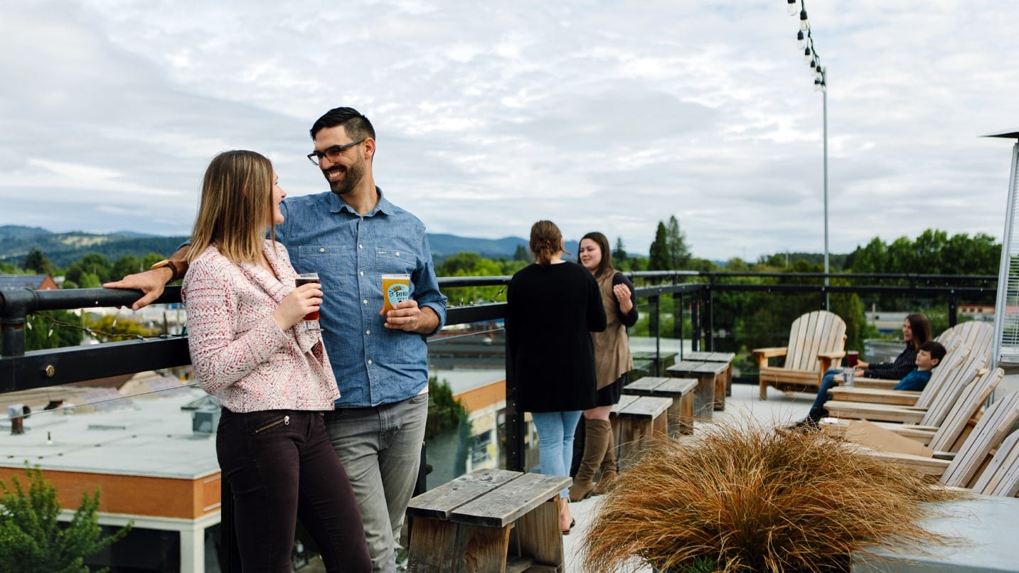Two pairs of people drinking beer on a rooftop deck