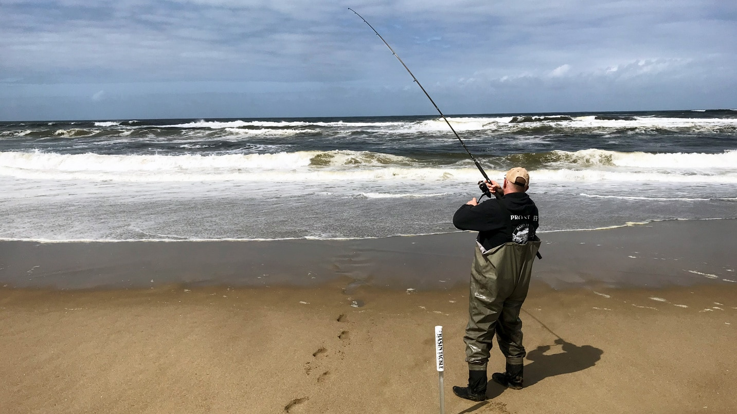 A fisherman casting a line into the ocean