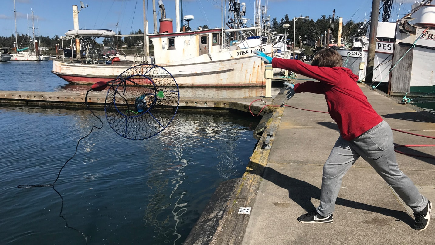A young boy throwing a crabbing net off of a dock