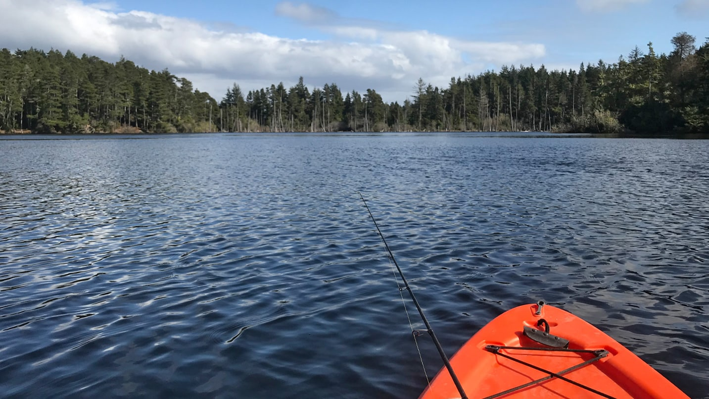 A fishing pole dangles off of the front of a kayak in a lake