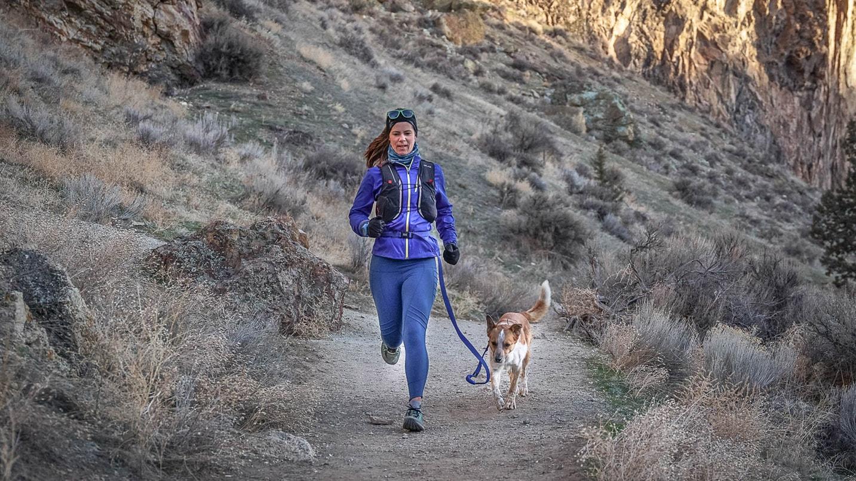 Jen Sotolongo runs down a path with Sitka.
