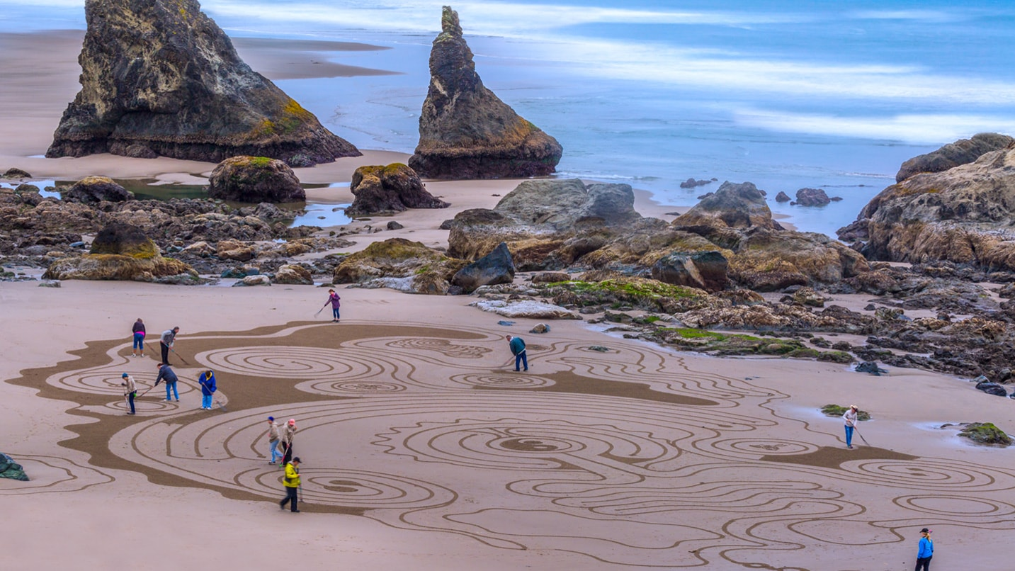 People walk through a sand labyrinth next to large rocks.