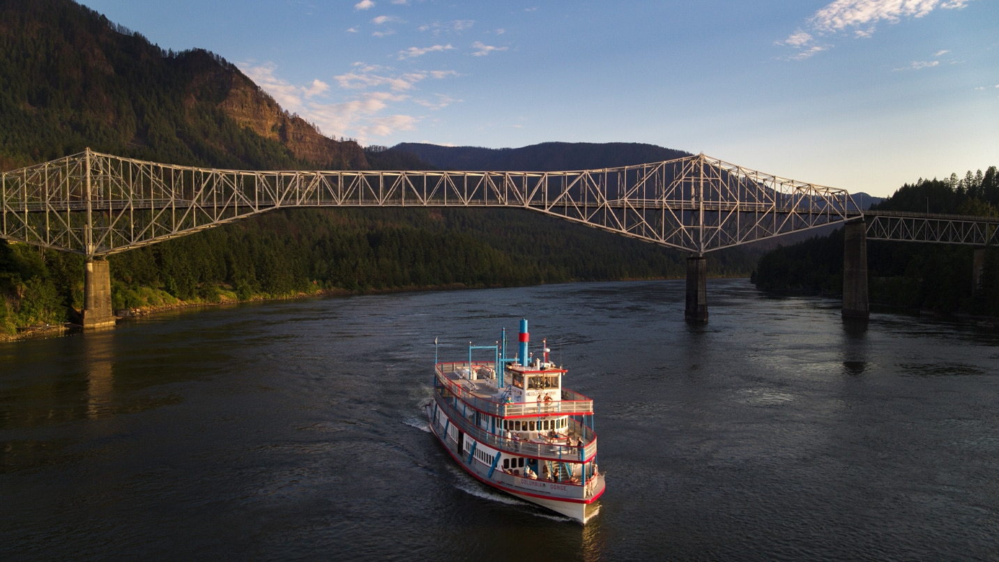 The red and white sternwheeler glides across the Columbia River.