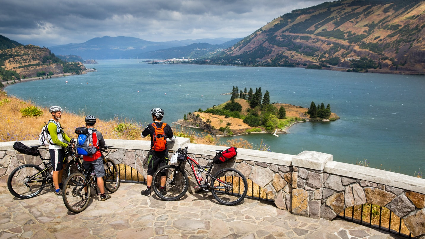 Three cyclists take a break at an overlook of the Columbia River.