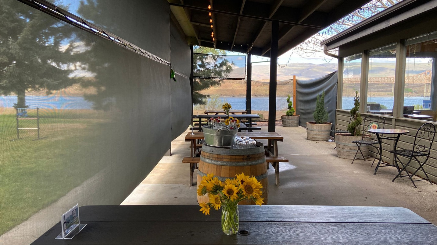 A covered patio stretches to a view of the blue Columbia River.