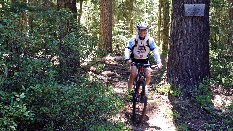 A mountain biker riding through a shady trail