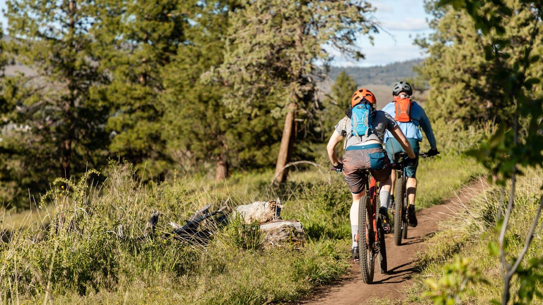 Two mountain bikers bike down a narrow trail