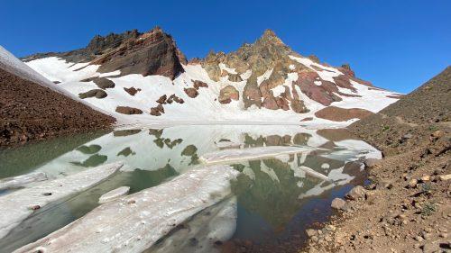 Snowmelt surrounds a high-altitude alpine lake.