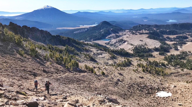 Two hikers walk uphill on a rocky terrain.