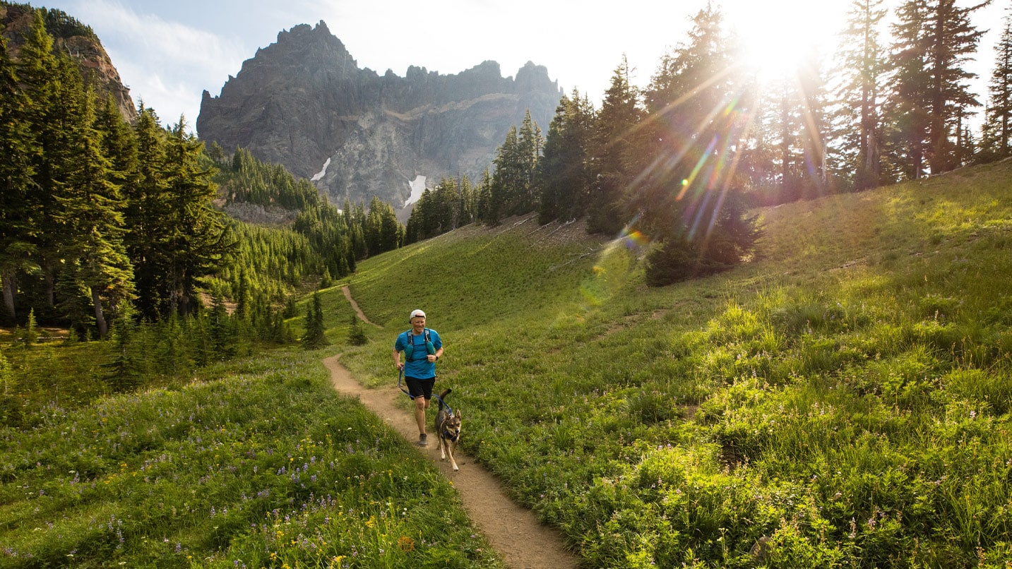 A runner goes down a dirt trail with Three Fingered Jack behind.