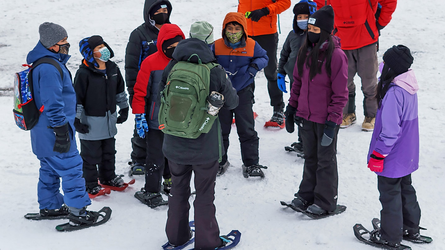 Snowshoers gather around an instructer in the snow.