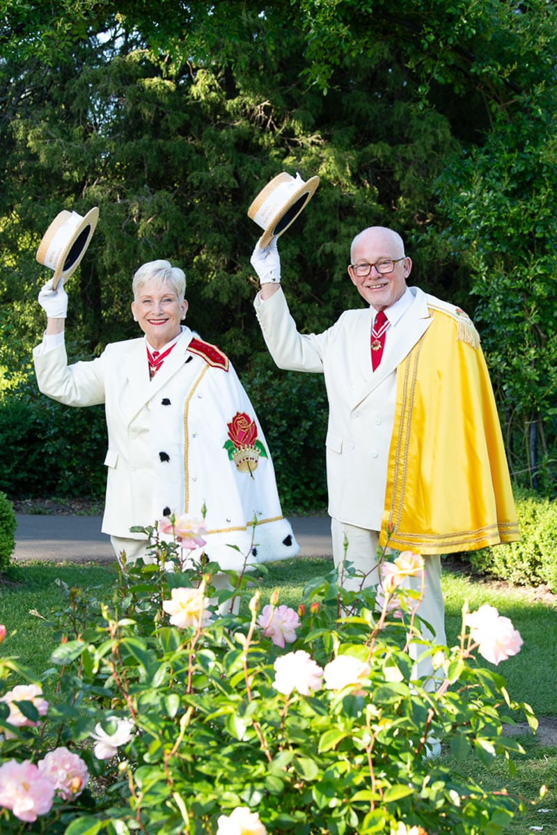 A female and male Rosarian in full white regalia tips their hats in a rose garden