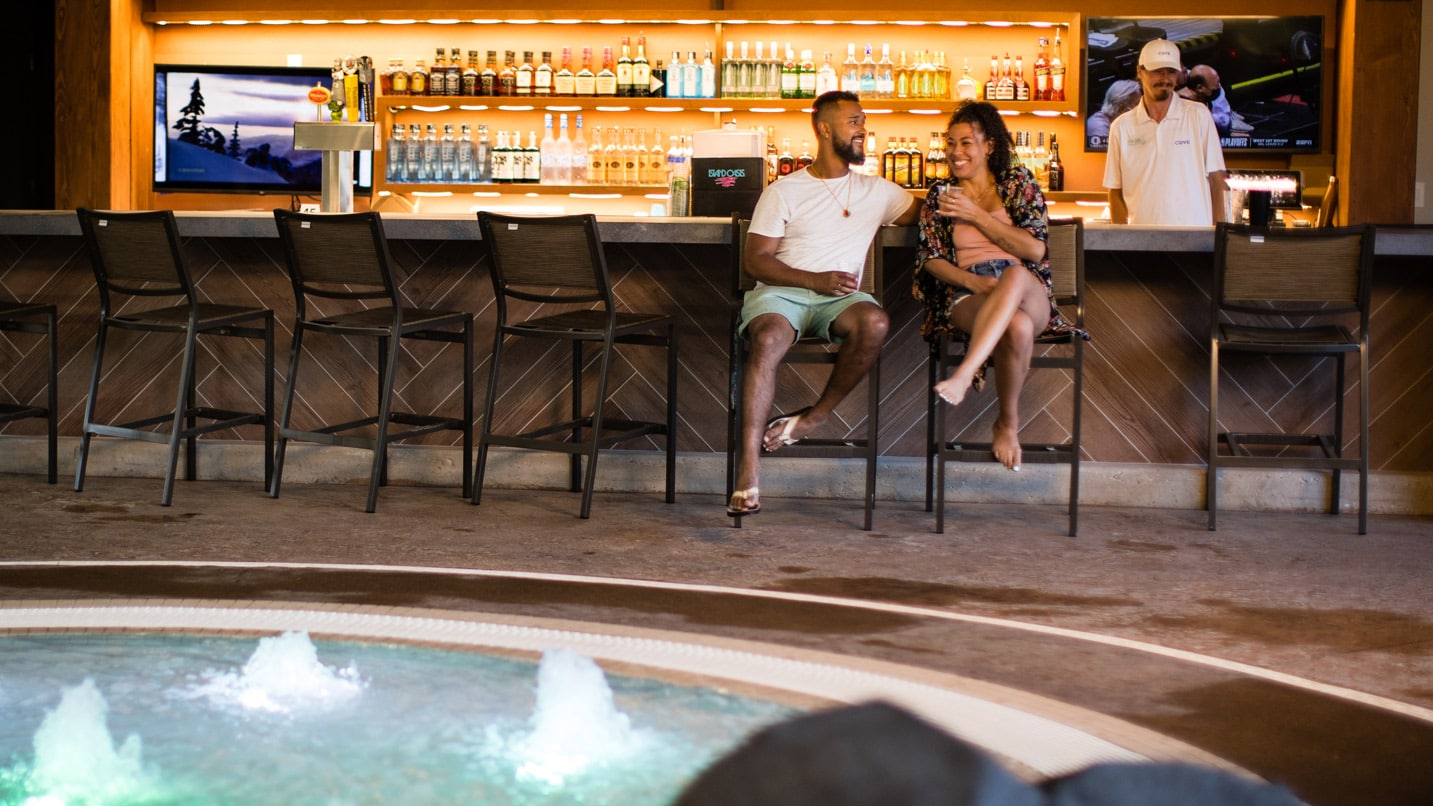 Two adults sit at an indoor poolside bar