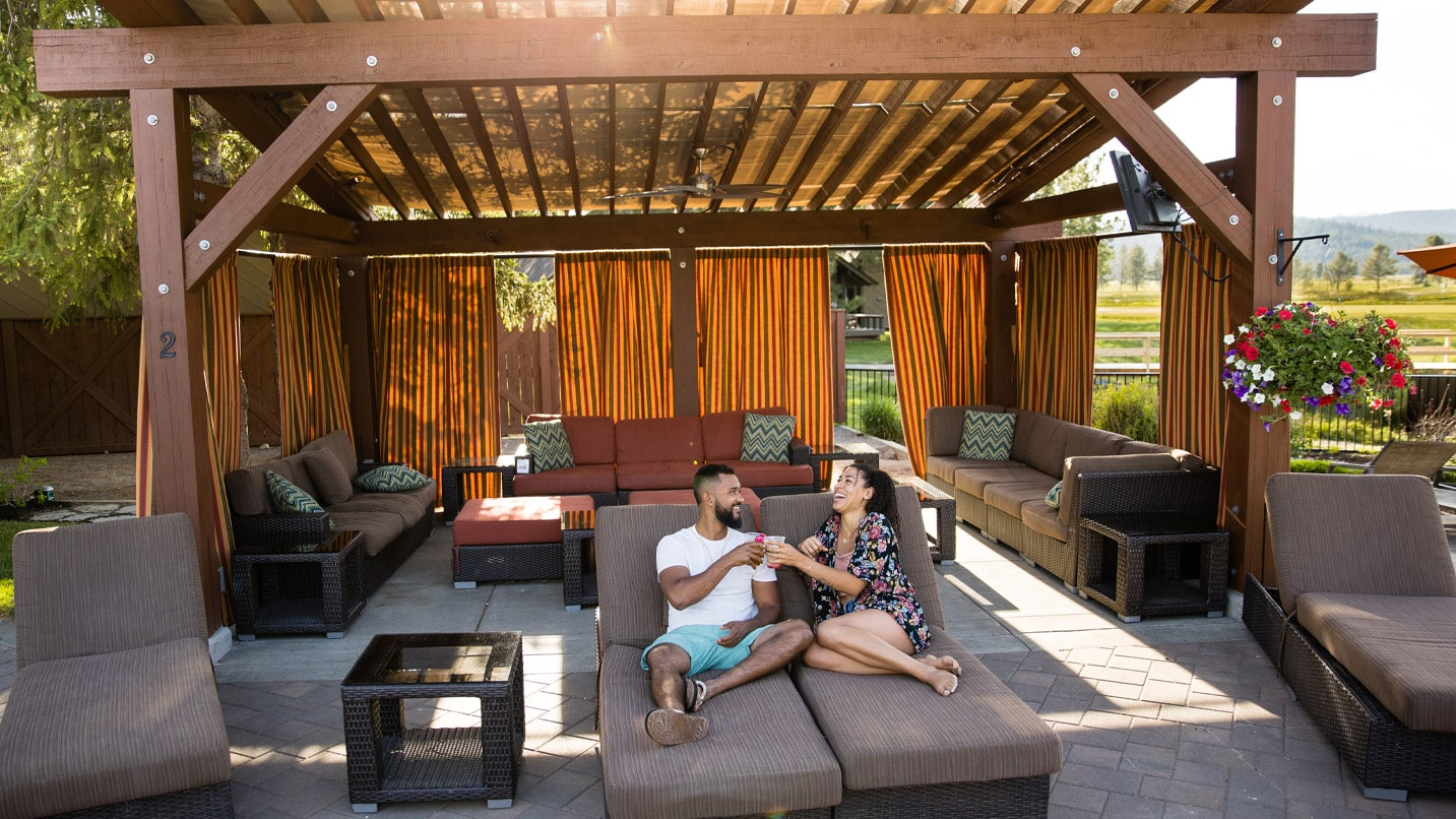 Two people lounge on a couch outdoors