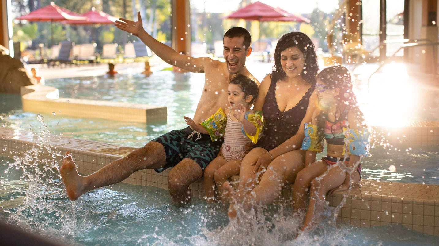 Two adults and two children splash on the edge of a pool