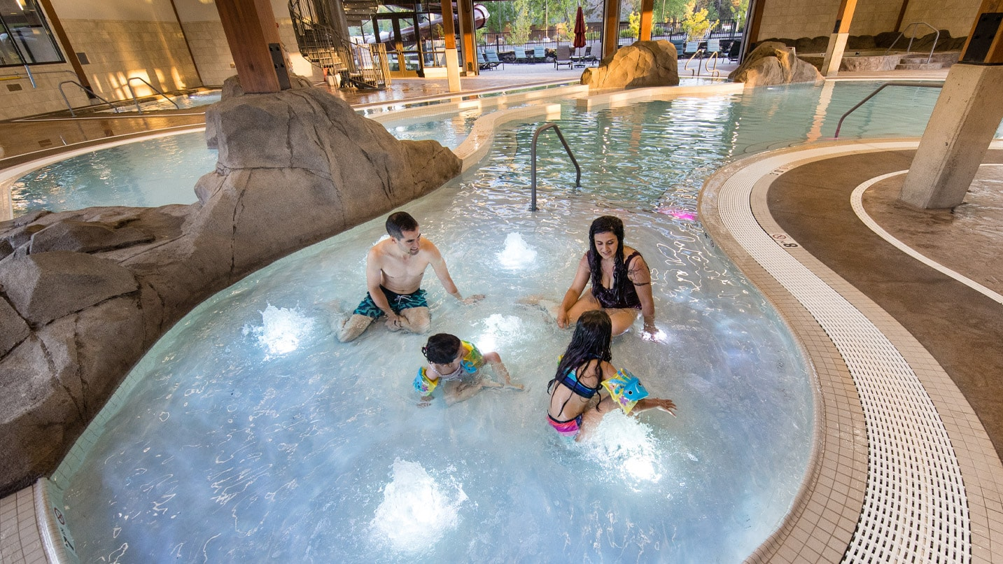 Two adults and two children sit in a large jetted hot tub