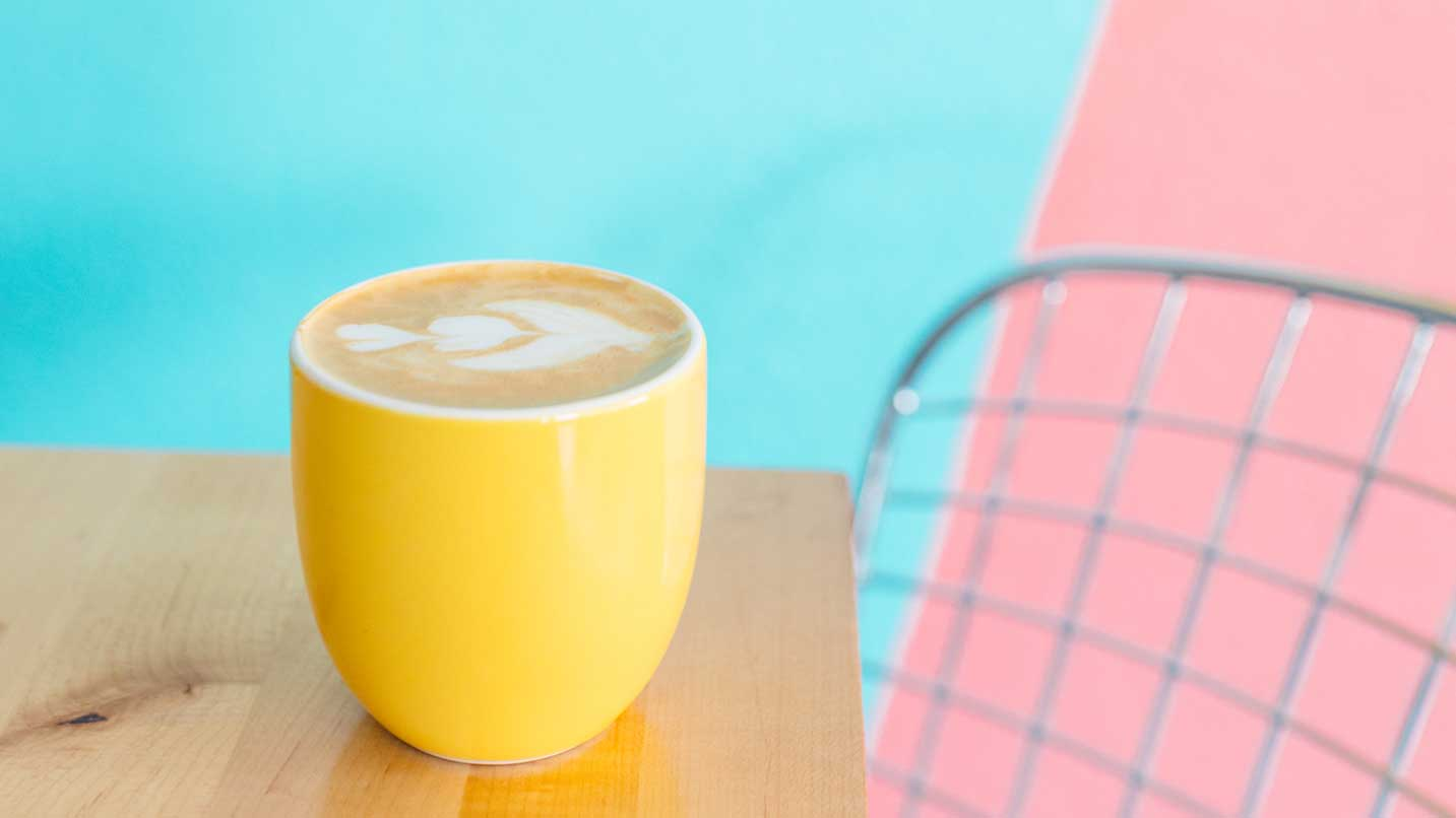 A yellow mug with coffee is placed on a table.