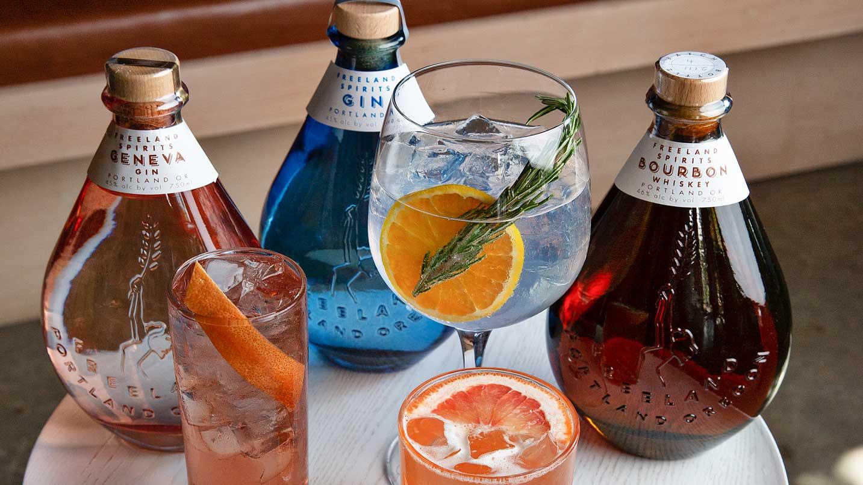Three bottles of spirits sit next to three mixed drinks.
