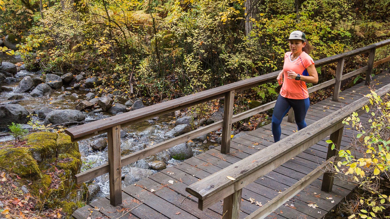 Running over a wooden trail bridge