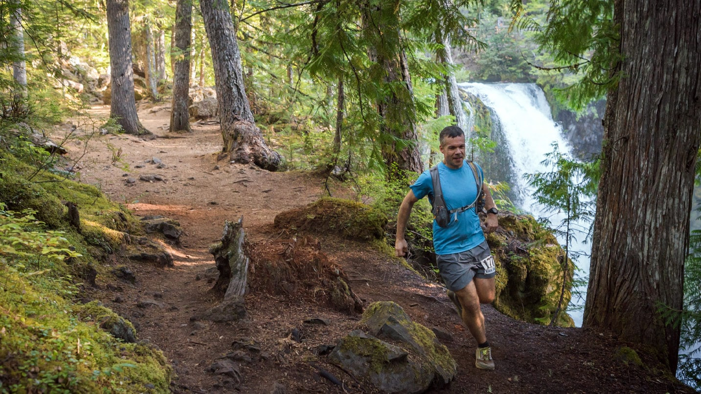 Running on a trail beside a waterfall