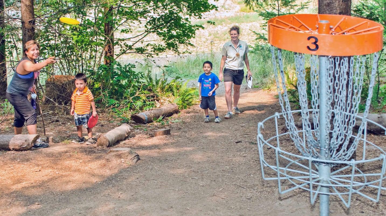 A family throws discs into a net