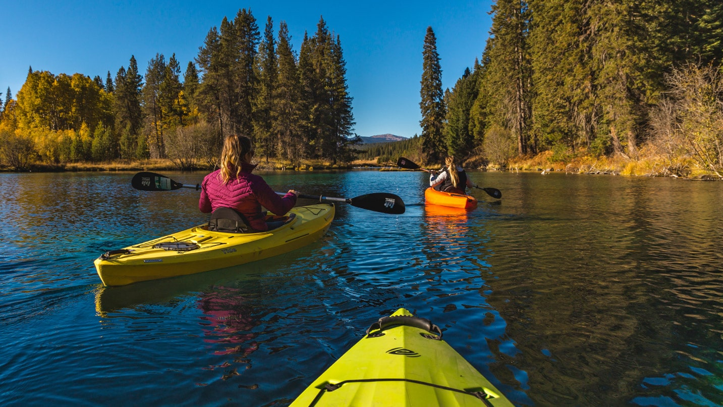 Three brightly colored kayaks skim along a river