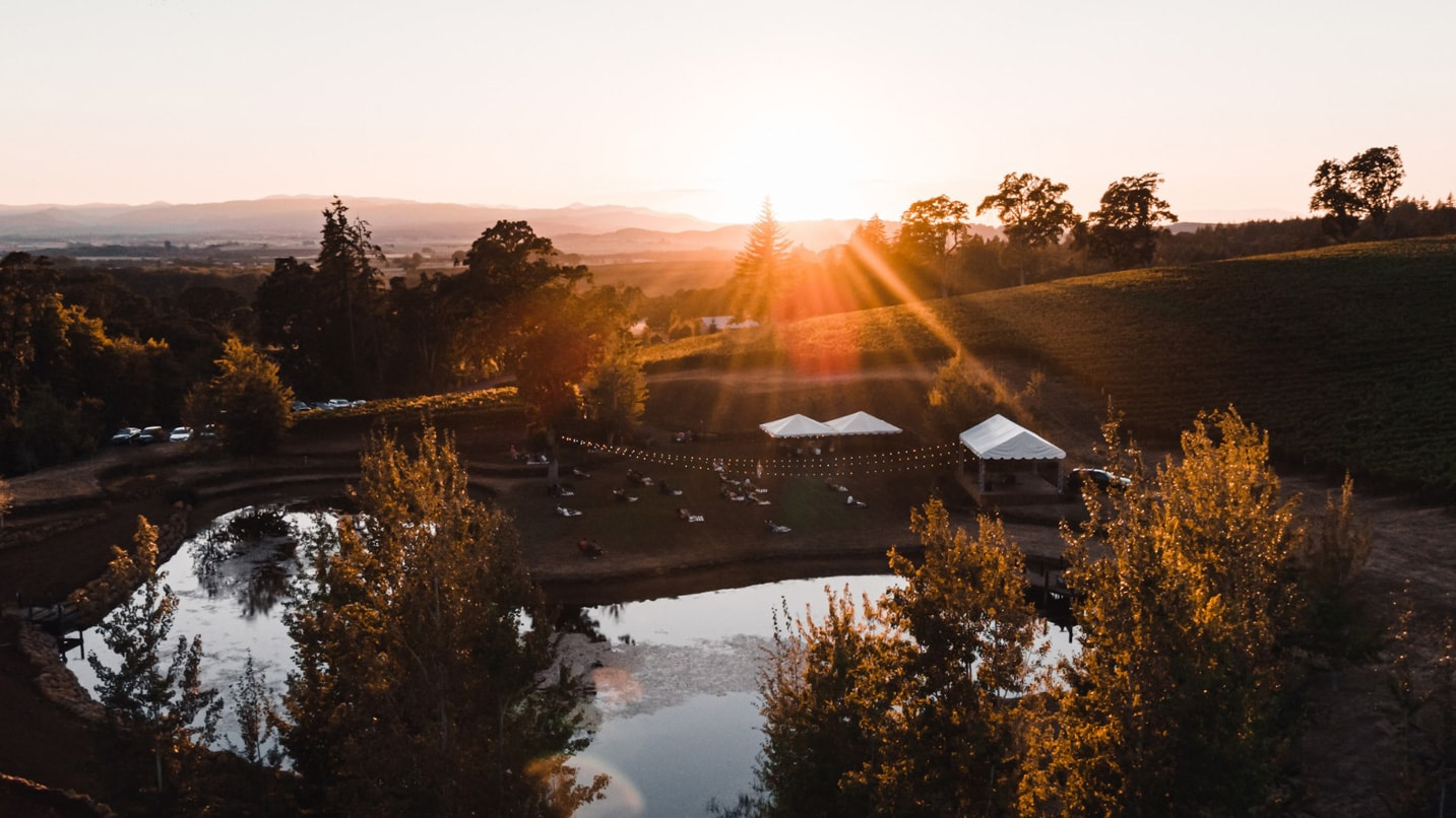 Tables are set up in a vineyard as the sun sets