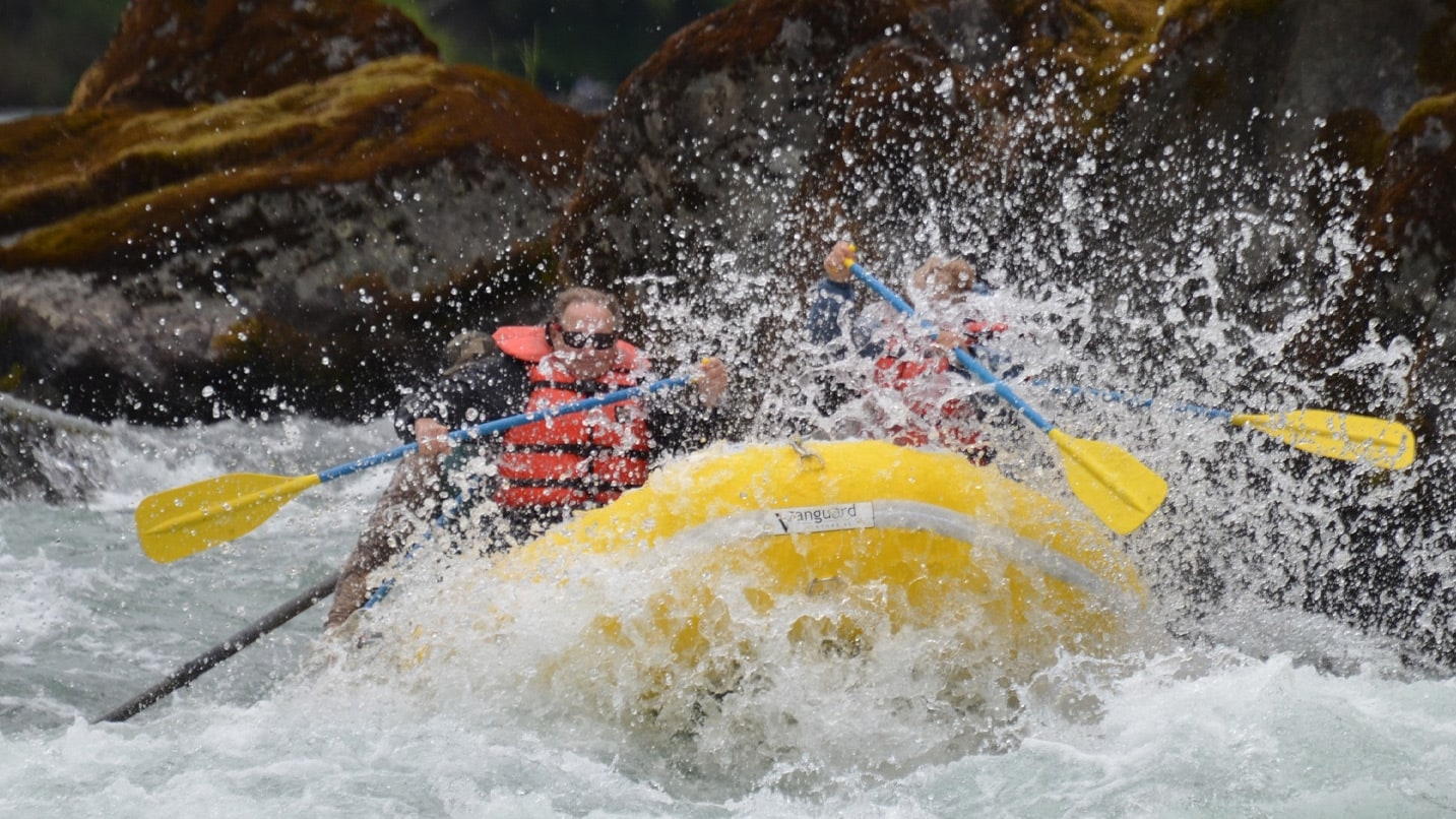 A yellow raft hits a river rapid