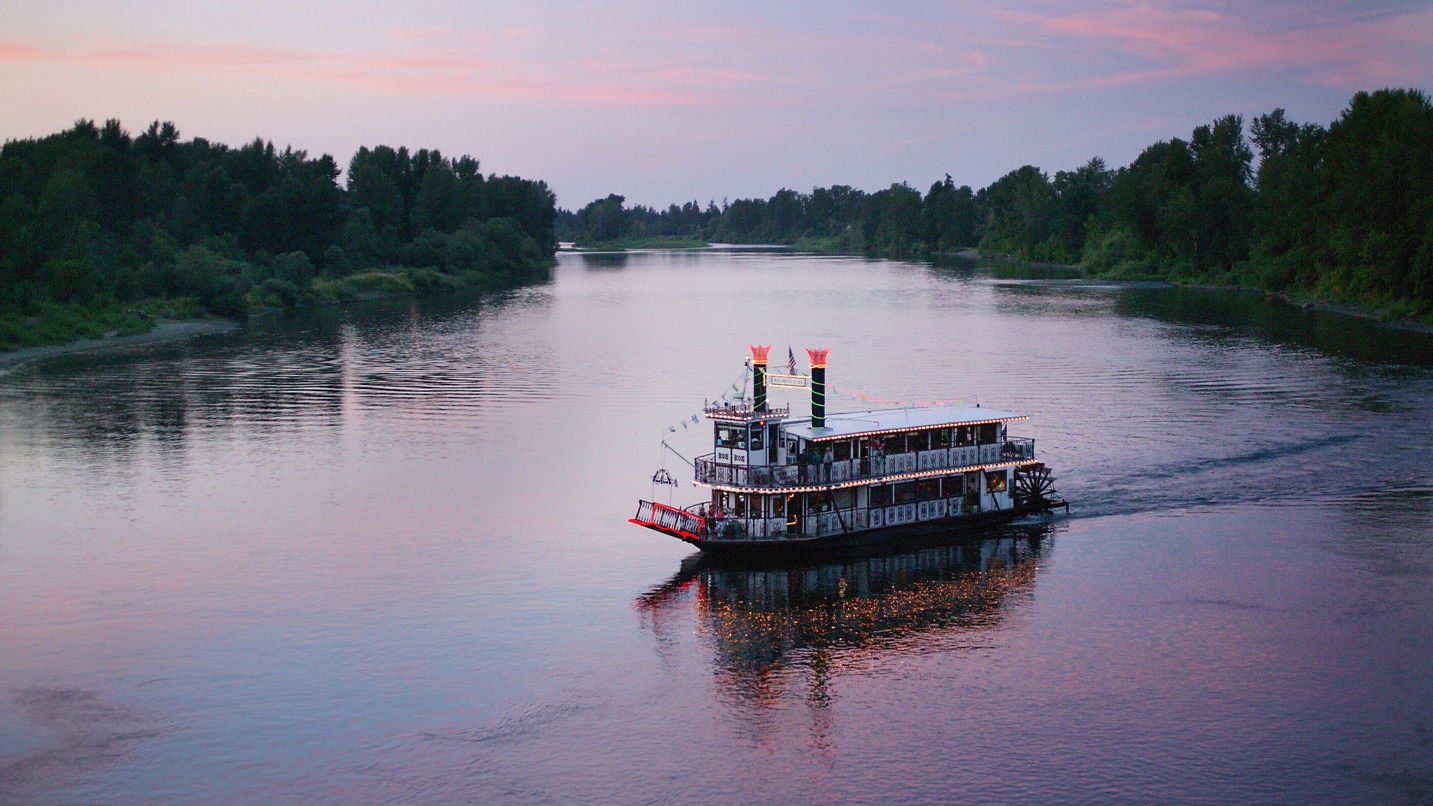 A paddlewheel boat glides across the river at sunset