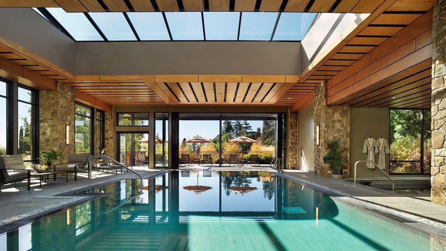 A pool is lit by expansive skylights