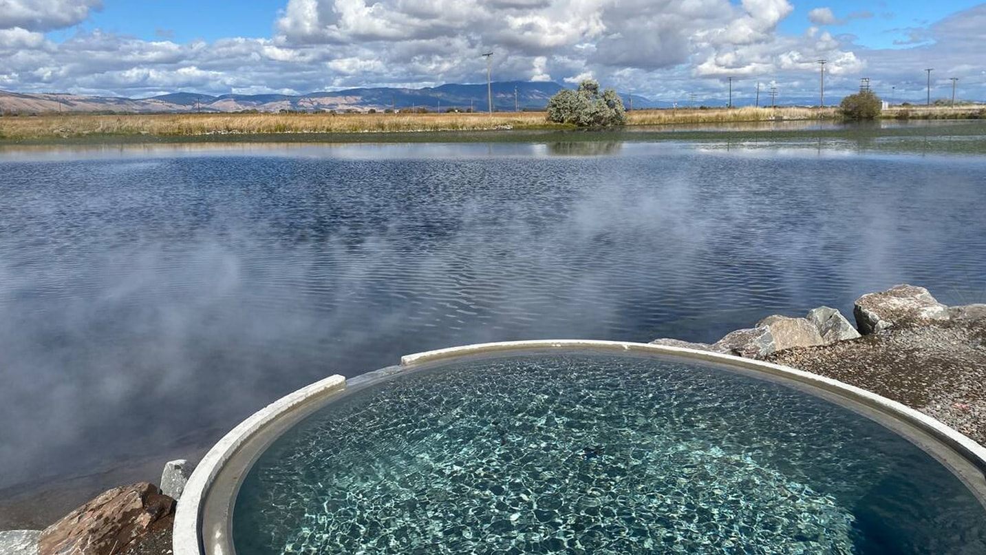 A hot springs pool sits at the edge of a lake