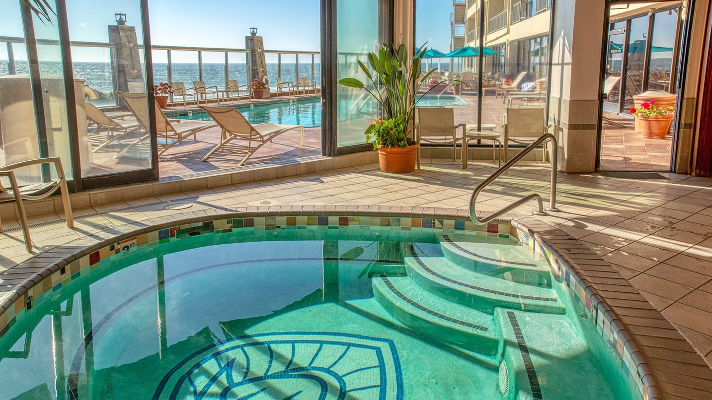 An indoor teardrop shaped spa opens up to an outdoor pool overlooking the ocean
