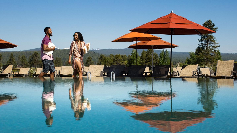 Two people walk alongside an infinity pool