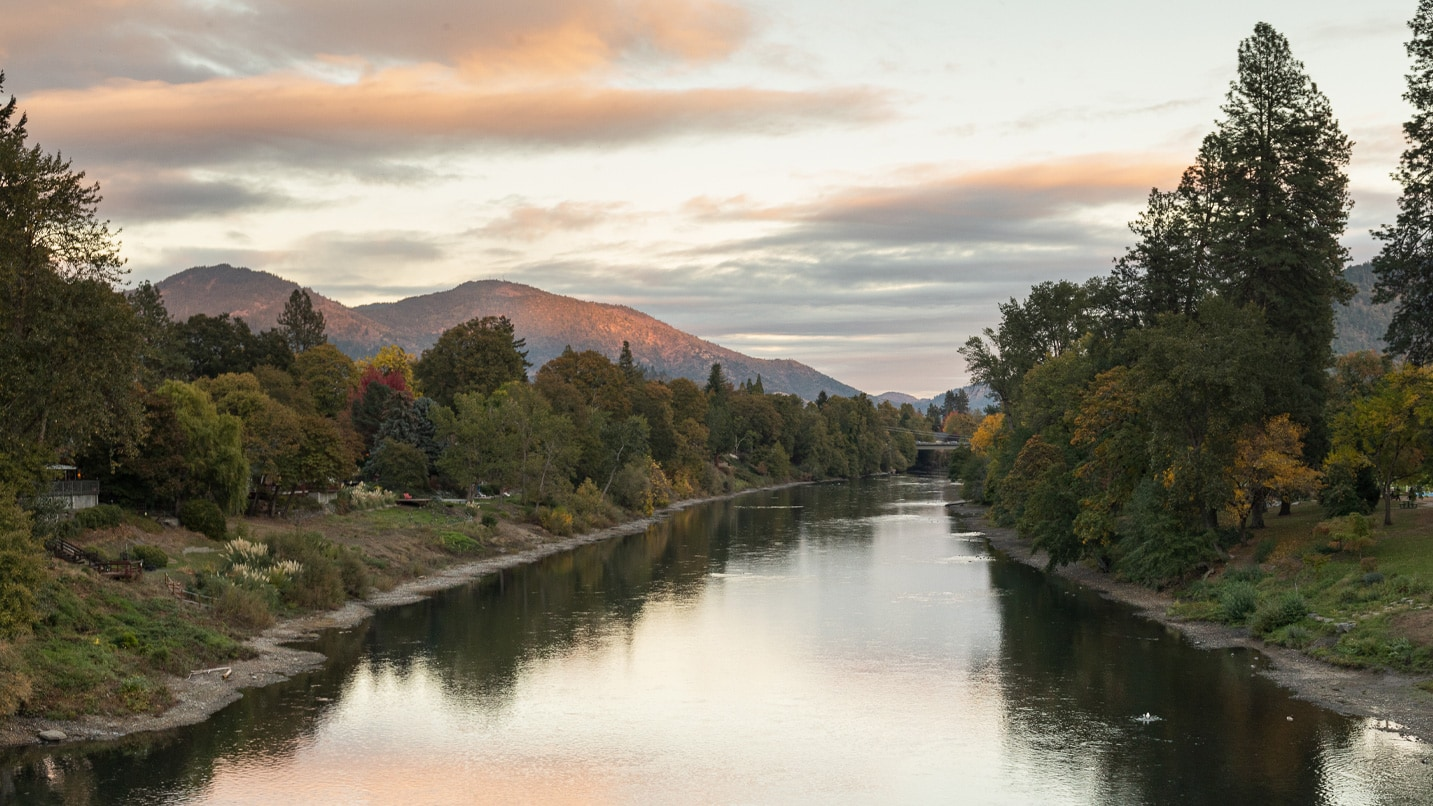 Trees reflect off the Rogue River at sunset.