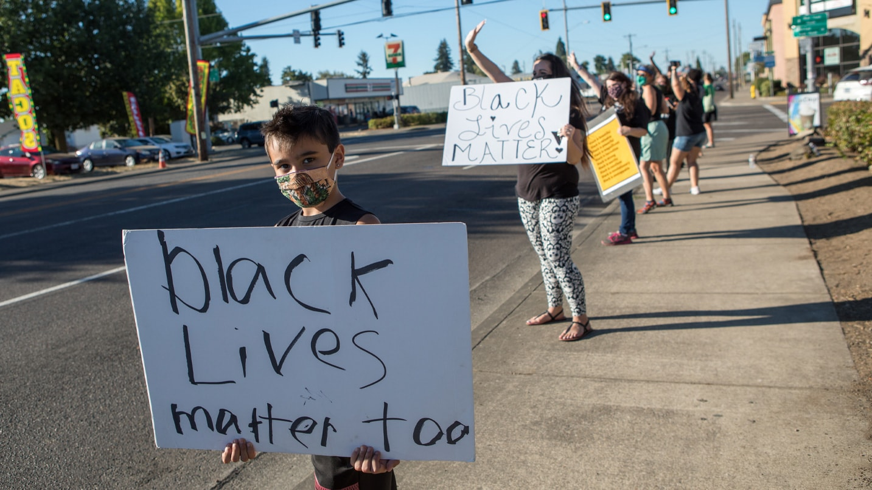 A masked boy holds a hand-painted Black Lives Matter sign.