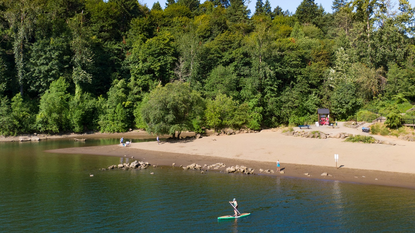 A person paddle boards in a calm river with a beach and playground in the background
