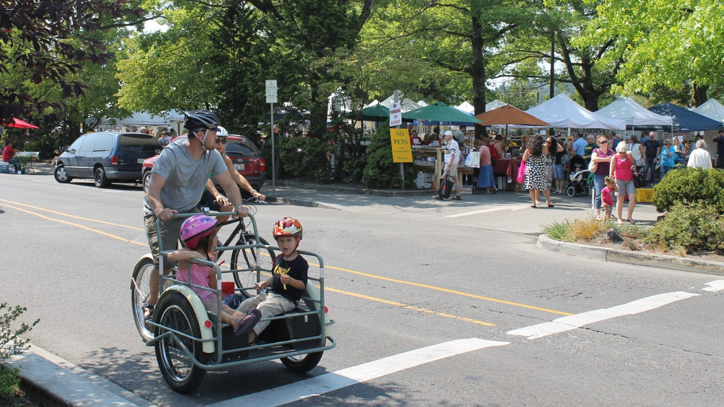 A man rides a bicycle with his kids in a trailer in front of him
