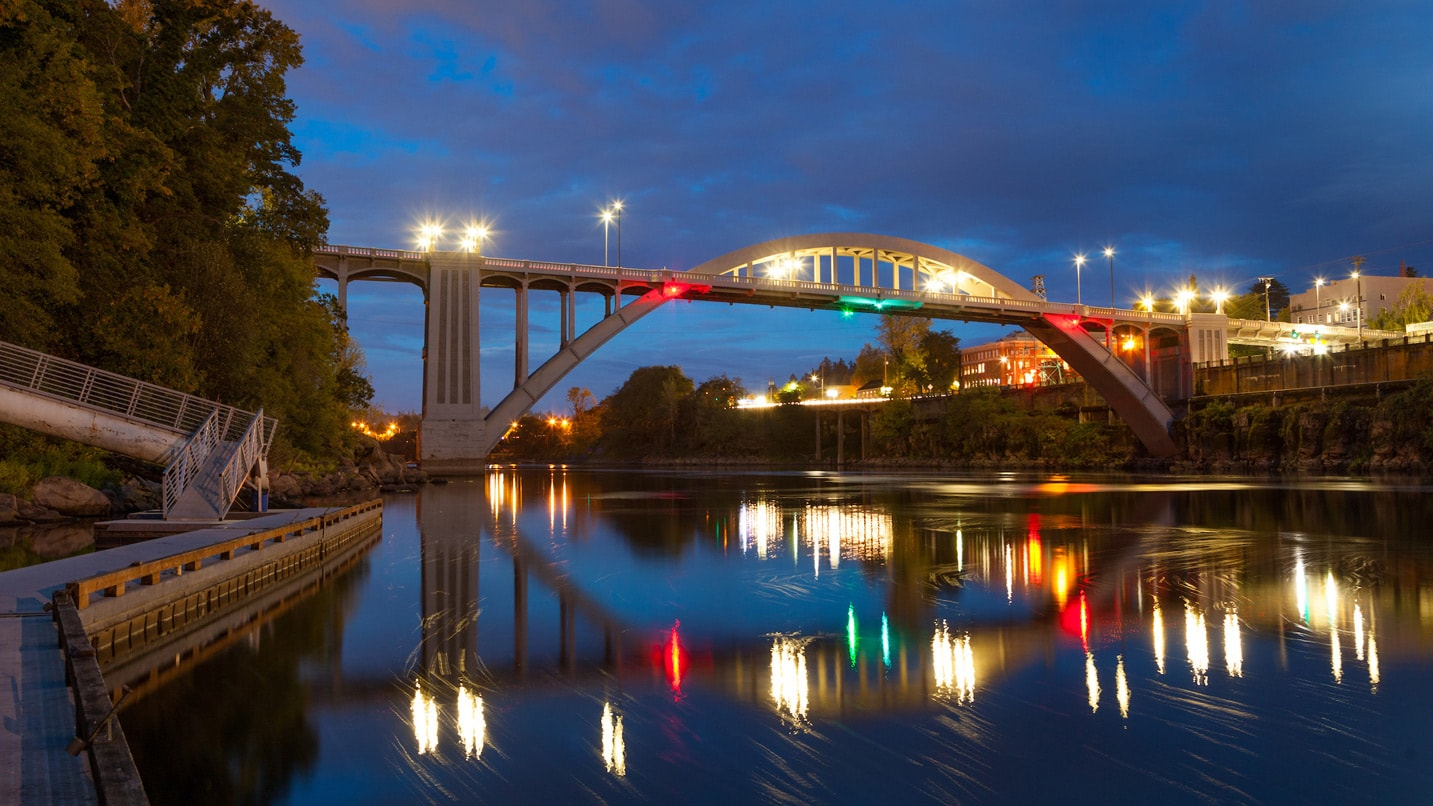 An arched bridge over the river at night