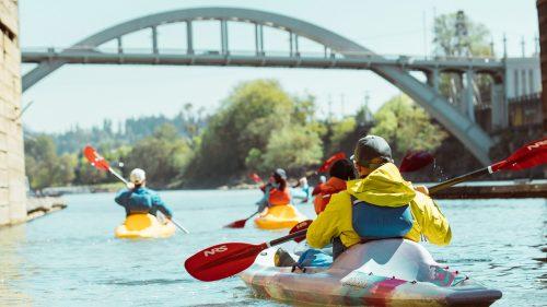 Kayakers paddle toward an arched bridge