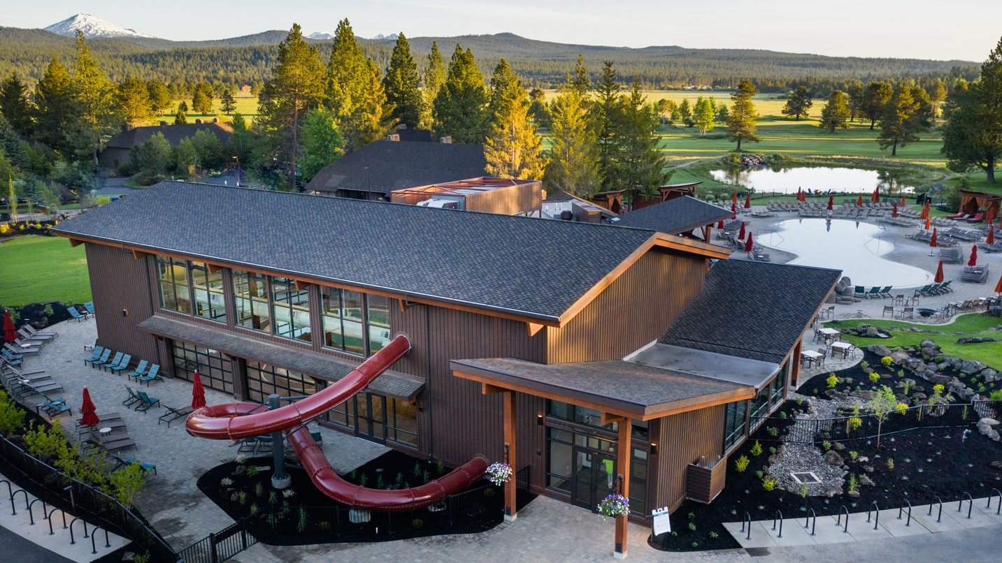 A tubed waterslide exits a building with views of mountains in the distance