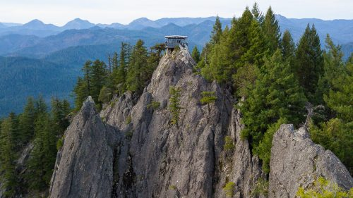 A small fire tower lookout is perched on top of rock with forested hills in the distance