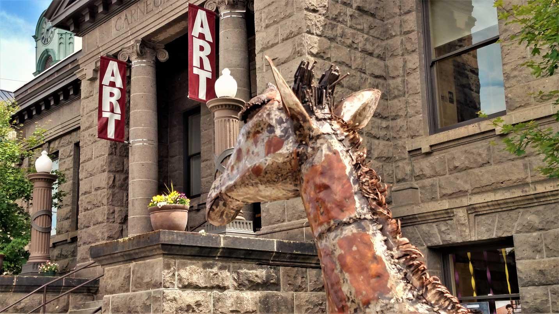 A metal giraffe statute sits outside a brick art gallery.