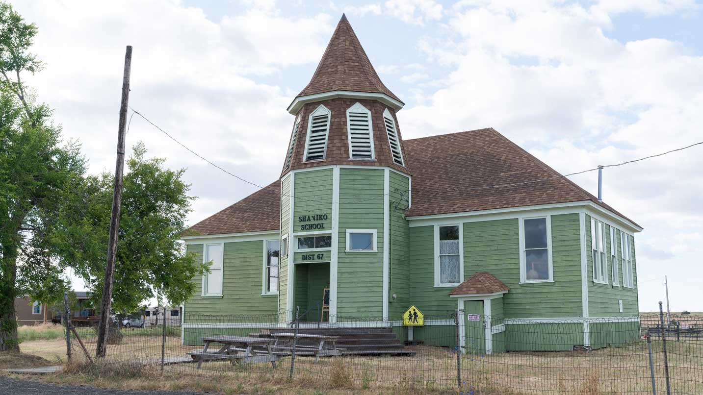 A faded green schoolhouse has a brown roof.