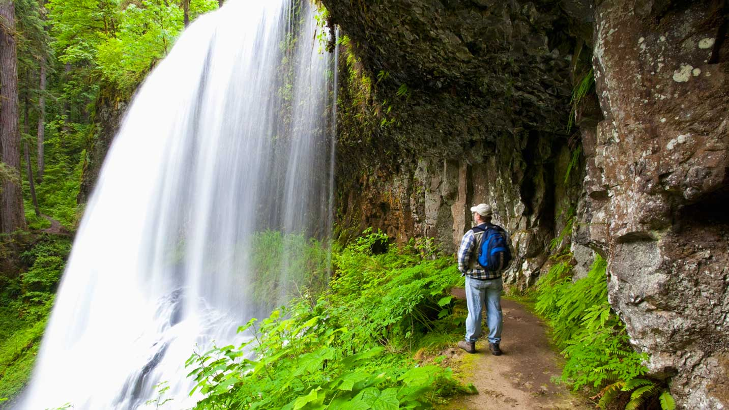A hiker stops to admire a gushing waterfall.