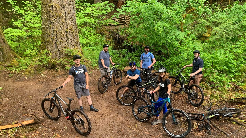 People smile next to their mountain bikes.