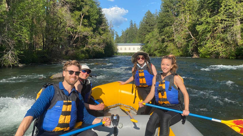 People wear life jackets in a raft.