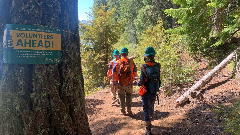 Helmeted volunteers walk down a trail.